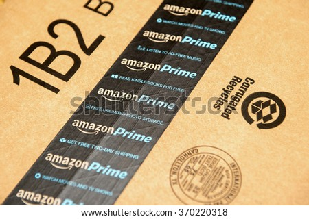 PARIS, FRANCE - JAN 28, 2016: Amazon Prime logotype printed on cardboard box security scotch tape. Prime is a service from Amazon which delivers parcels in 1 day, streams unlimited music and video - stock photo