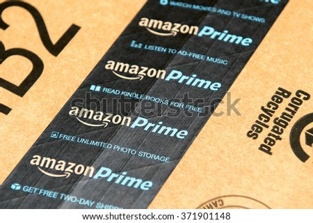 PARIS, FRANCE - JAN 28, 2016: Amazon Prime logotype printed on cardboard box security scotch tape. Amazon Prime is a service from Amazon which delivers parcels in 1 day, streams unlimited music - stock photo