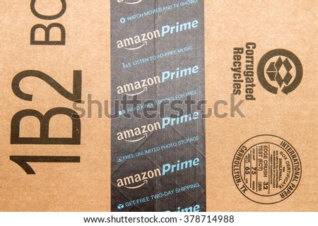 PARIS, FRANCE - JAN 28, 2016: Amazon Prime logotype printed on cardboard box security scotch tape. Amazon Prime is a service Amazon which delivers parcels in 1 day, streams unlimited music and video - stock photo