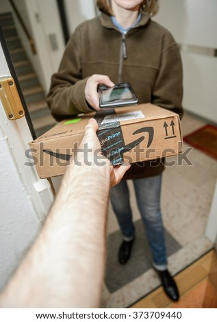 PARIS, FRANCE - JAN 27, 2016: Customer hand taking the parcel as the UPS United Parcel Service young female postal delivery courier in front of door scans package from Amazon Prime  - stock photo