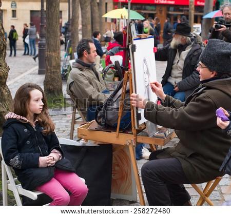 PARIS, FRANCE - JAN 17, 2015: Unidentified artist drawing a portrait of the tourist at Place du Tertre, Montmartre. Place du Tertre is now an open-air workshop with its 288 official painters.  - stock photo