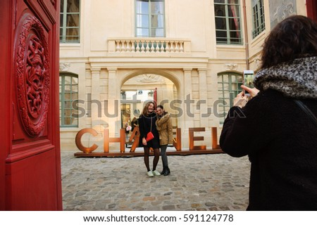 PARIS, FRANCE - JANUARY 28, 2017: Chanel shop in old Marais quarter. Chanel fashion house founded by Coco Chanel is symbol of haute couture and luxury goods. Young girls take photo with brand sign.