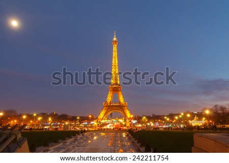 Paris, France - January 1, 2015: Eiffel Tower with electric lighting in the late evening. The tower is the most famous and popular tourist attraction in Paris. - stock photo