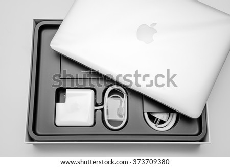 PARIS, FRANCE - JANUARY 14, 2015: New Apple MacBook Pro laptop covered by the plastic film and all its accesories in the box seen from above during the unboxing process - stock photo