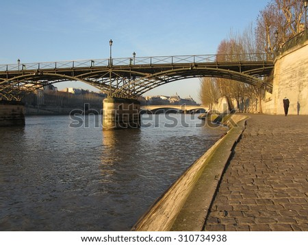 PARIS, FRANCE - JANUARY 3, 2010: Paris bridge crossing the river Seine in morning sunlight from the right bank on January 3, 2010 in Paris, France.