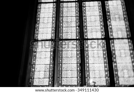 PARIS, FRANCE - JANUARY 23, 2013: Stained glass with beautiful floral ornament seen with a tilt-shift lens to obtain the defocused effect - stock photo