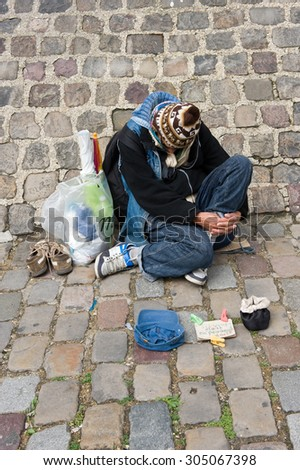 PARIS, FRANCE - JULY 27, 2015: A homeless man is sitting and begging for money on a street in Paris in France - stock photo