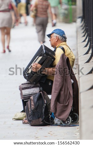 PARIS, FRANCE - JULY 27, 2013: An accordion player sitting on a bridge in Paris and plays French songs. Paris is the most visited city in the world with 15.6 million international arrivals in 2011. - stock photo
