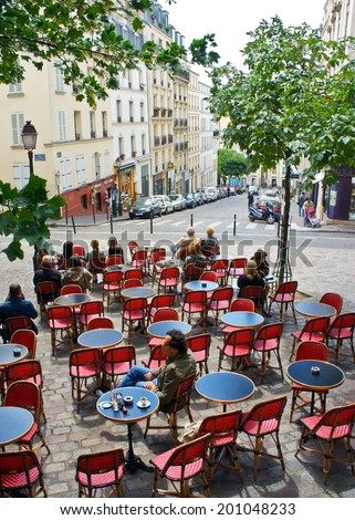 Paris, France - July 17, 2011 - Diners enjoy the sun at an outdoor cafe in Montmartre, Paris. The cafe lifestyle is a draw for the millions of tourists who visit Paris each year.