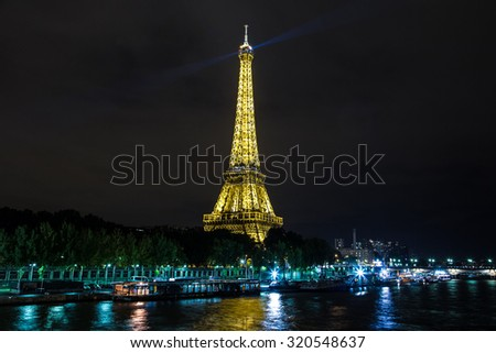 PARIS, FRANCE - JULY 14 2014: Eiffel Tower at sunset is the most visited monument in France and the most famous symbol of Paris, July 14, 2014