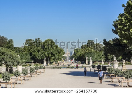 PARIS, FRANCE - JULY 13, 2012: Jardin des Tuileries (Tuileries garden) - favorite spot for rest of tourists and Parisians. Garden was created by Catherine de Medici in 1564. - stock photo