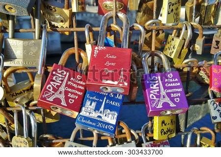 PARIS, FRANCE - JULY 29, 2015: Lockers on the bridge. Hanging lockers on bridges is popular romantic tradition among loving couples visiting Paris. - stock photo