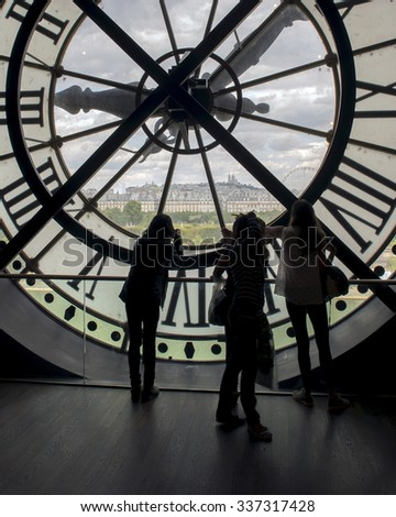 PARIS, FRANCE - JULY 25, 2015: Silhouettes of unidentified tourists looking through the clock with roman numerals in the museum D'Orsay - stock photo