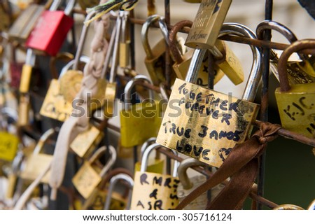PARIS, FRANCE - JULY 28, 2015: Thousands of padlocks on a fence near the Pont des Arts symbolize 'love forever' in Paris in France - stock photo