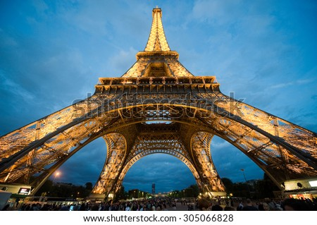 PARIS, FRANCE - JULY 27, 2015: Tourists are visiting the eiffel tower in the twilight in Paris in France - stock photo