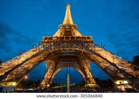 PARIS, FRANCE - JULY 27, 2015: Tourists are visiting the eiffel tower in the twilight in Paris in France