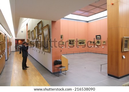 PARIS, FRANCE - JULY 22, 2011: Visitor admires paintings in Louvre Museum, Paris, France. With 8.5m annual visitors, Louvre is consistently the most visited museum worldwide.