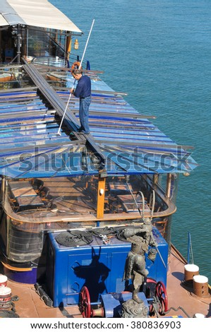 Paris, France - July 9, 2015: Worker cleans the roof of a restaurant boat overlooks the quays of Seine in Paris, France