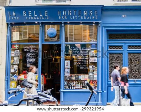 PARIS, FRANCE - JUNE 21; La belle Hortense famous wine bar and bookshop in Marais District Paris France with people walking past the open door on June 21, 2009 in Paris France. - stock photo