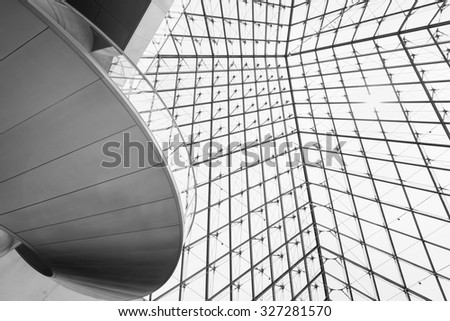 PARIS, FRANCE - June 13, 2014:Louvre Pyramid Paris view from below angle with architectural details of glass steel pyramid and Louvre Stairs with counter sun light in black and white.  - stock photo