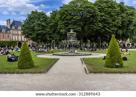 PARIS, FRANCE - JUNE 10, 2015: People relaxing on green lawns of famous Place des Vosges - oldest planned square in Paris, in Marais district. Place des Vosges was built by Henri IV from 1605 to 1612.