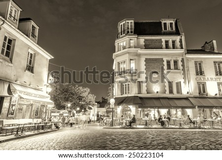 PARIS, FRANCE - JUNE 20, 2014: Tourists enjoy Montmartre city life on a beautiful night. More than 30 million people visit Paris every year. - stock photo