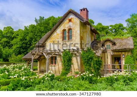 PARIS, FRANCE - JUNE1, 2015: Tourists visiting the Hameau de la Reine, The Queen's Hamlet is a rustic retreat in Versailles, Paris, France - stock photo