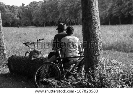 PARIS, FRANCE - JUNE 14, 2013: Unidentified man and woman rest and smoke in Vincennes park after biking.  Vincennes park is  the largest park of Paris which is very popular on weekends among Parisians