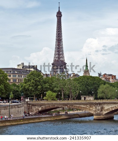 PARIS, FRANCE - JUNE 9, 2014: View of the Eiffel Tower with a bridge in the foreground.