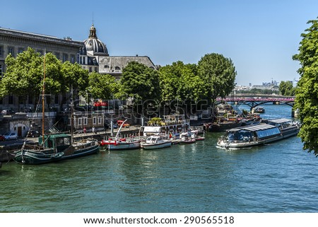 PARIS, FRANCE - JUNE 8, 2015: View of the Seine River with cruise tour boats. In Paris there are several boat tourist trips across the Seine to show tourists the sights of interest.