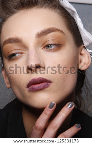 PARIS, FRANCE - MARCH 06: A model gets ready backstage at the Kenzo fashion show during Paris Fashion Week on March 6, 2011 in Paris, France.