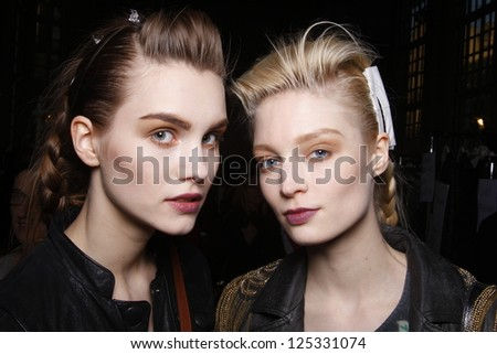 PARIS, FRANCE - MARCH 06: A pair of models get ready backstage at the Kenzo fashion show during Paris Fashion Week on March 6, 2011 in Paris, France. - stock photo