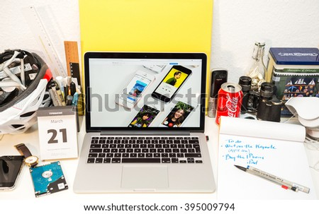 PARIS, FRANCE - MARCH 21, 2016: Apple Computers website on MacBook Pro Retina in a geek creative room environment showcasing the newly announced iPhone SE with diverse media on screen - stock photo