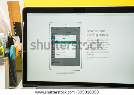 PARIS, FRANCE - MARCH 21, 2016: Apple Computers website on MacBook Pro Retina in a geek creative room environment showcasing the newly announced iPad Pro and tata plans in the US for Apple Sim - stock photo
