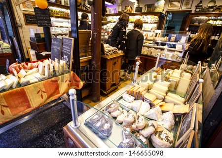 PARIS, FRANCE - MARCH 29 : French cheese shop with dozens of kinds of chees and customers choosing among them on March 29th 2013 in Paris, France  - stock photo