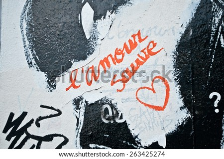 """PARIS - FRANCE - 22 March 2015 - graffiti on the wall with message in french """"l'amour sauve"""" traduction in english """"Love Saves"""" - stock photo"""