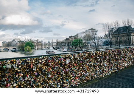 PARIS, FRANCE - MARCH 23, 2013: Love locks on a fence on the access ramp to the Pont des Arts over the River Seine in Paris which is covered with thousands of padlocks. Focus on background.