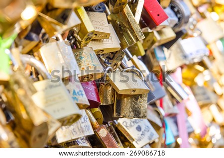 "PARIS, FRANCE MARCH 17- 2015: Love locks on the bridge ""Pont des Arts"" across river Seine. - stock photo"