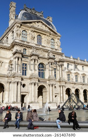 PARIS, FRANCE, March 12, 2015 : People rest in Louvre Palace courtyard. Louvre is a former royal palace located on the Right Bank of the Seine in Paris, and now a museum. - stock photo