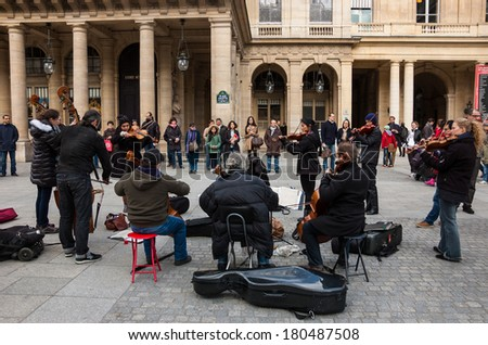 PARIS, FRANCE - MARCH 2, 2014: Small string orchestra plays at Comedie Francaise square before audience consisting mainly of tourists. Dozens buskers perform on the streets and in metro of Paris. - stock photo