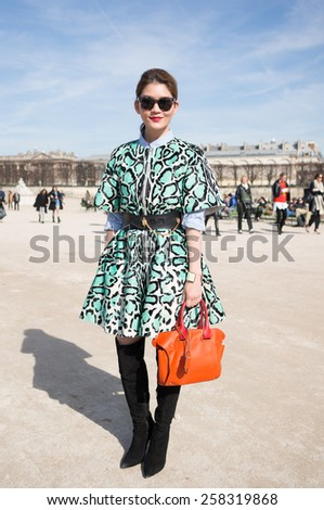 PARIS, FRANCE - MARCH 6, 2015: Stylish Asian woman with green and black pattern skirt in the Tuileries Garden. Paris Fashion Week: Ready to Wear 2015/2016 is held from March 3 to 11, 2015. - stock photo