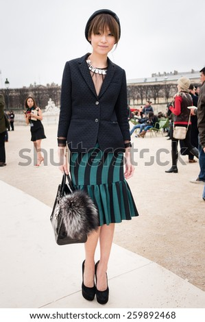 PARIS, FRANCE - MARCH 10, 2015: Stylish Asian woman with green and black striped skirt in the Tuileries Garden. Paris Fashion Week: Ready to Wear 2015/2016 is held from March 3 to 11, 2015. - stock photo