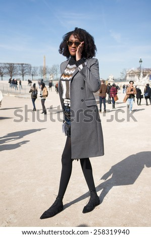 PARIS, FRANCE - MARCH 6, 2015: Stylish black woman with black leaather in the Tuileries Garden. Paris Fashion Week: Ready to Wear 2015/2016 is held from March 3 to 11, 2015. - stock photo