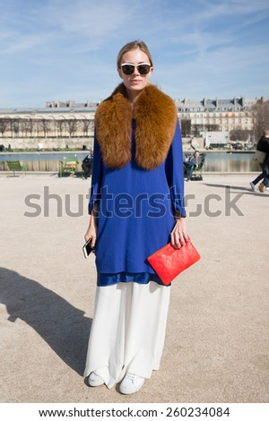 PARIS, FRANCE - MARCH 6, 2015: Stylish European woman with blue dress. Paris Fashion Week: Ready to Wear 2015/2016 is held from March 3 to 11, 2015. - stock photo