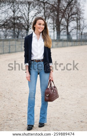 PARIS, FRANCE - MARCH 10, 2015: Stylish European woman with blue jeans in the Tuileries Garden. Paris Fashion Week: Ready to Wear 2015/2016 is held from March 3 to 11, 2015. - stock photo