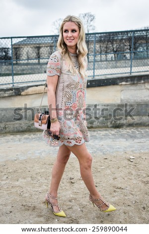 PARIS, FRANCE - MARCH 10, 2015: Stylish European woman with plant motif skirt in the Tuileries Garden. Paris Fashion Week: Ready to Wear 2015/2016 is held from March 3 to 11, 2015. - stock photo