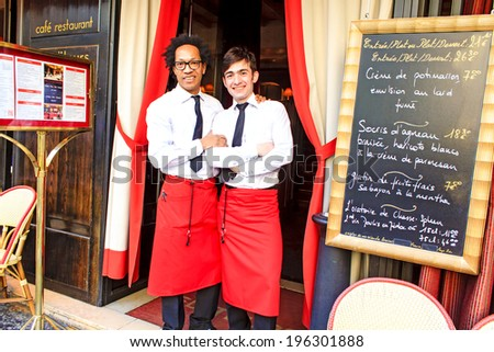 PARIS, FRANCE - MARCH 12 : Two waiters of the french restaurant near Odeon in Paris posing together at the restaurant door by the menu board on March 12th, 2014 in Paris, France - stock photo