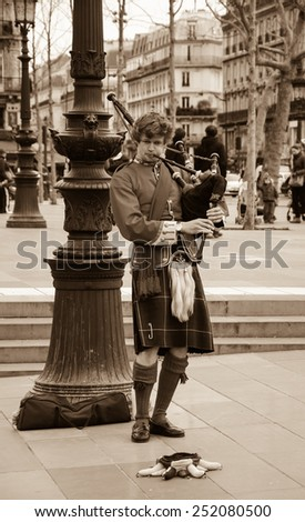 PARIS, FRANCE - MARCH 2, 2014: Young Scottish bagpiper in traditional costume plays music at Place de la Republique before the public. Dozens buskers perform on the streets and in metro of Paris. - stock photo