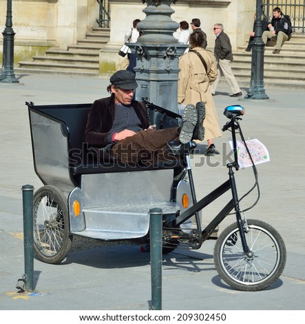 PARIS, FRANCE - MAY 03 2014: A Parisian trishaw waits a client in the spring street of the French capital PARIS, FRANCE - MAY 03 2014.