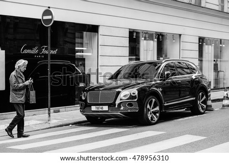 PARIS, FRANCE - MAY 21, 2016: Black and white of man taking photo of the luxury Bentley Bentayga Hybrid SUV on the streets of Paris, France- street fastion